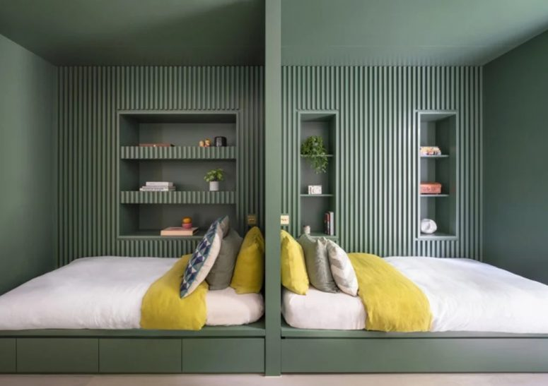 Here's a peaceful double bedroom done in greens, with wooden slabs and niches for storage