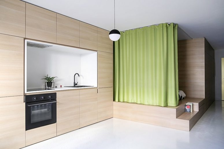 The apartment is an open space divided into zones with a lime curtain