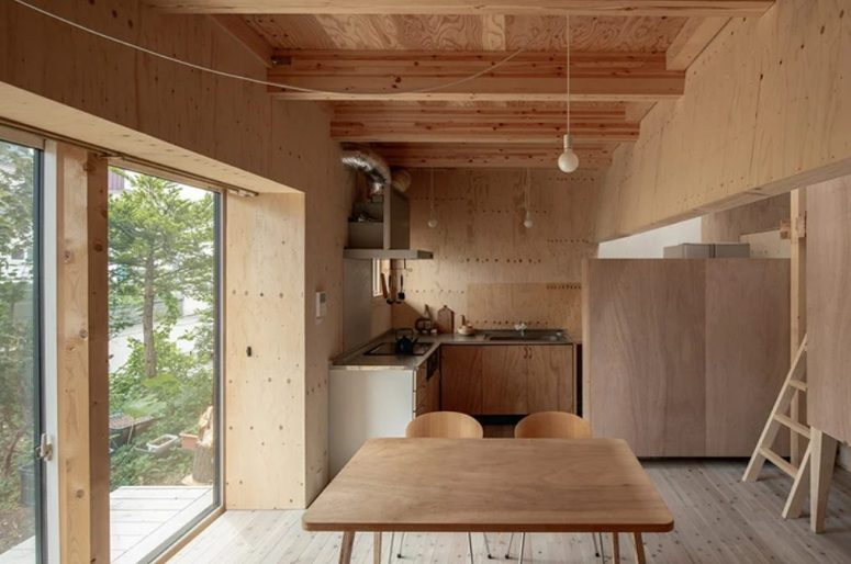 The kitchen and dining space are united into one, with simple wood and plywood furniture, pendant bulbs and a glazed wall with an entrance to the backyard