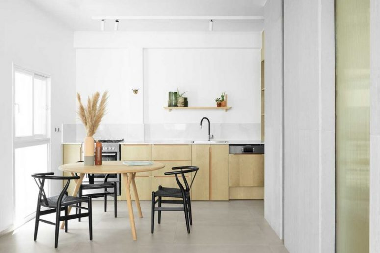 The kitchen is neutral, with white tiles, a stylish table and black chairs, everything is cool and chic