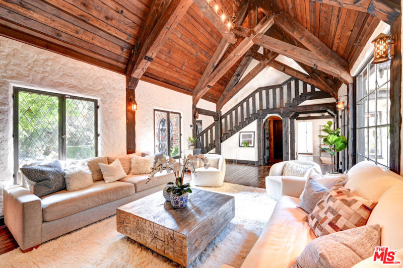 This barn living room is done with a wooden ceiling and beams, chic furniture and stone walls