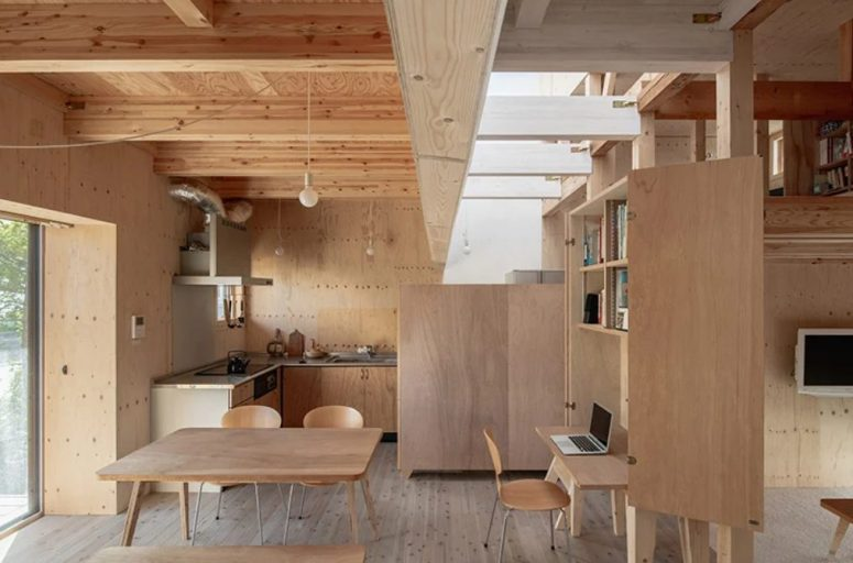 A large storage unit with a hidden desk divides the meal spaces and the living room, and skylights make them feel fresh