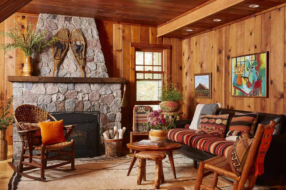 The living room is done with stained wood, vintage rustic furniture and a large stone hearth