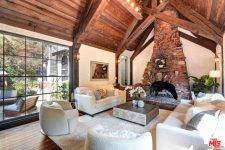 03 There's a large fireplace, a glazed wall and a mini wooden table