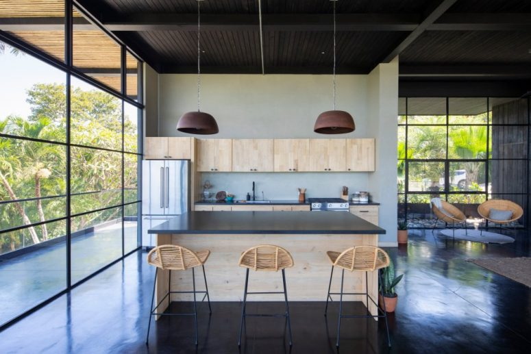 The kitchen is done with light-colored plywood cabinets, dark stone countertops and hanging lamps
