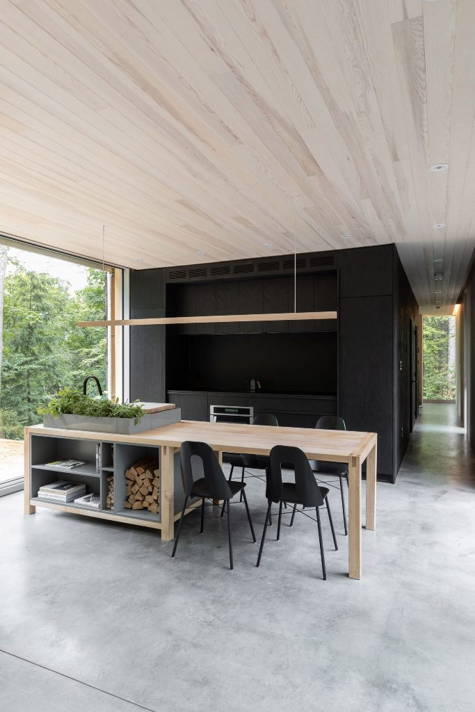 The kitchen is done in black, there's a wood and stone kitchen island that doubles as a dining table