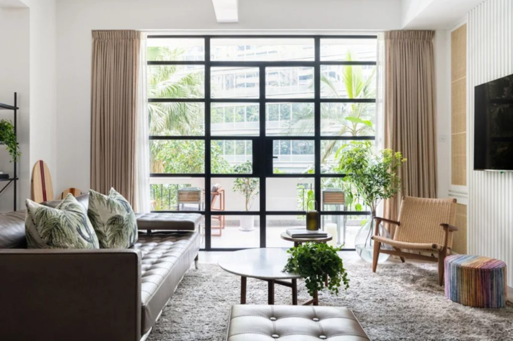 The living room is done with a leather sofa and ottoman, with a woven chair and a glazed wall that is an entrance to a terrace