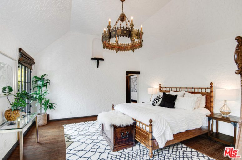The master bedroom is done with a gorgeous chandelier, a wooden chest and a chic bed