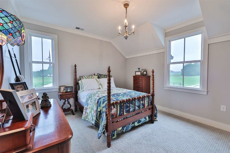 The master bedroom is done with heavy dark furniture, elegant lamps and printed bedding