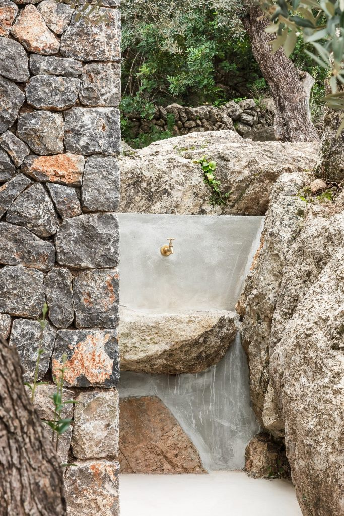 The sink is carved of stone outdoors and it features an elegant gold faucet