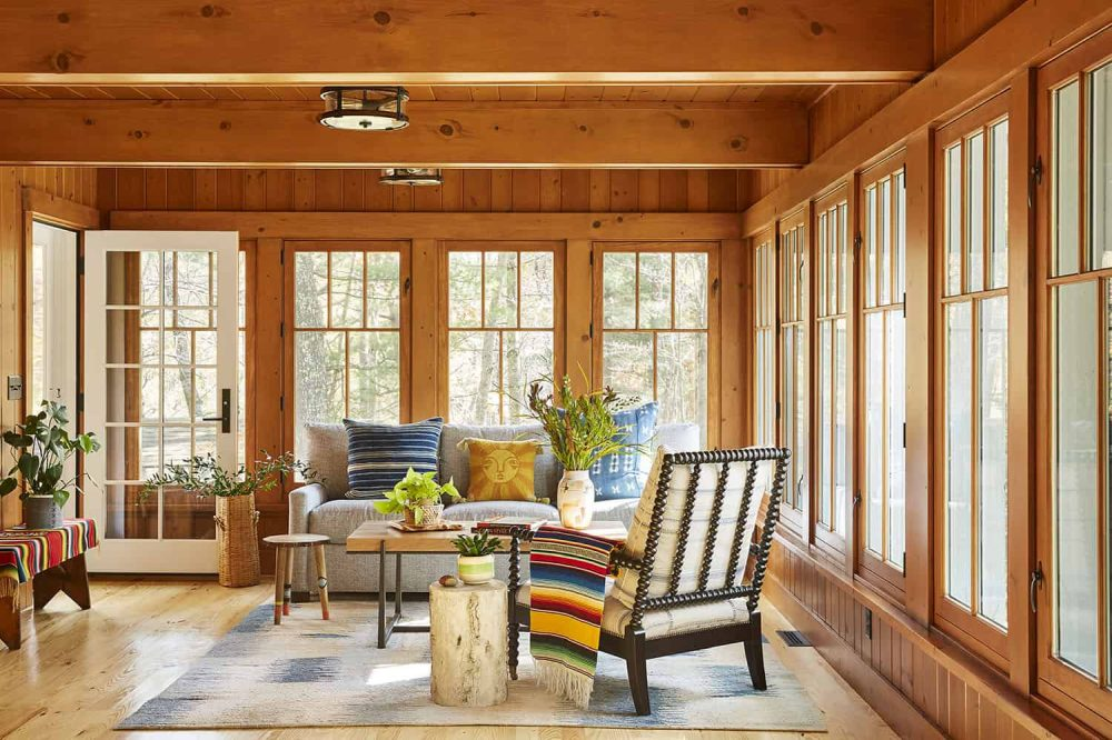 The sunroom is bright and fun, with bold textiles and lots of potted plants