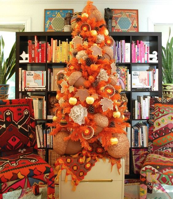 a beautiful fall tree in orange, with pinecones, citrus, oversized acorns and ornaments is very unusual