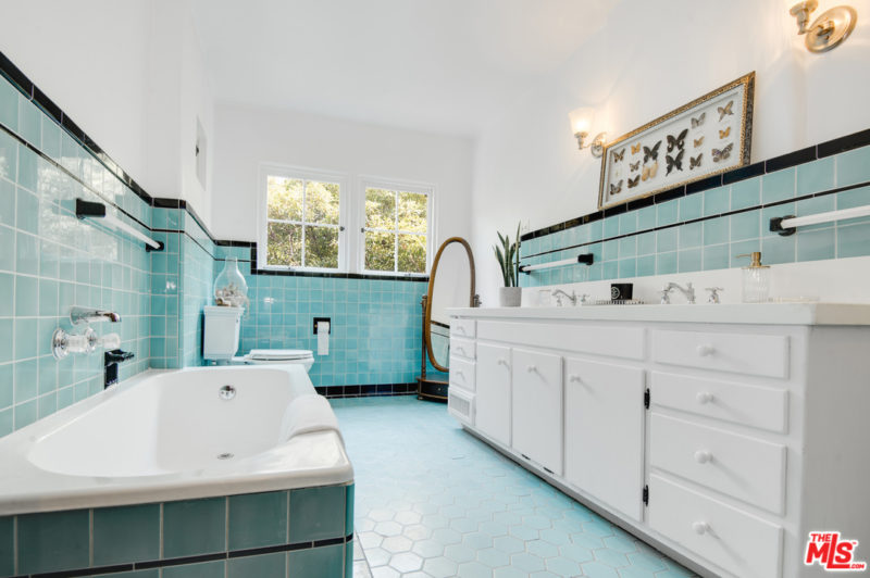 The bathroom is done with light blue tiles, a bathtub clad with tiles and a white vanity