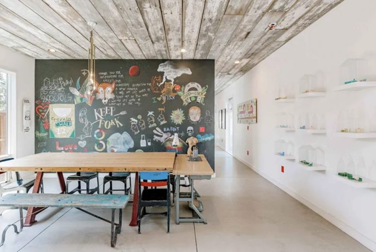 The dining zone features a bold art wall and mismatching chairs and benches for a shabby chic feel