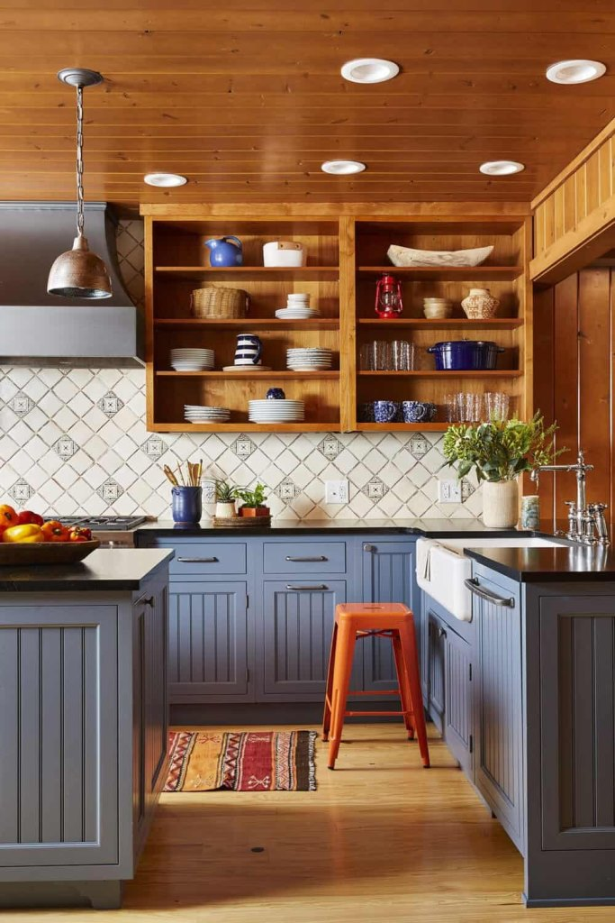 The kitchen is done in blues, with stained wooden shelving instead of upper cabinets and metal stools and lamps