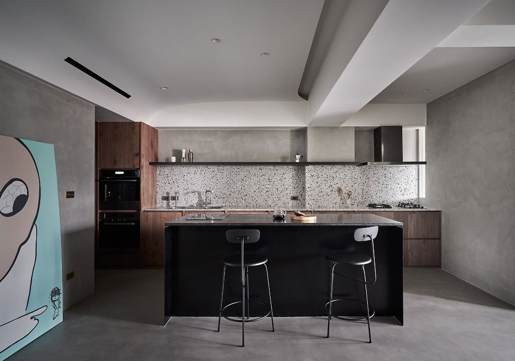 The kitchen is done with stained wooden cabinets, a black kitchen island and a cool terrazzo backsplash