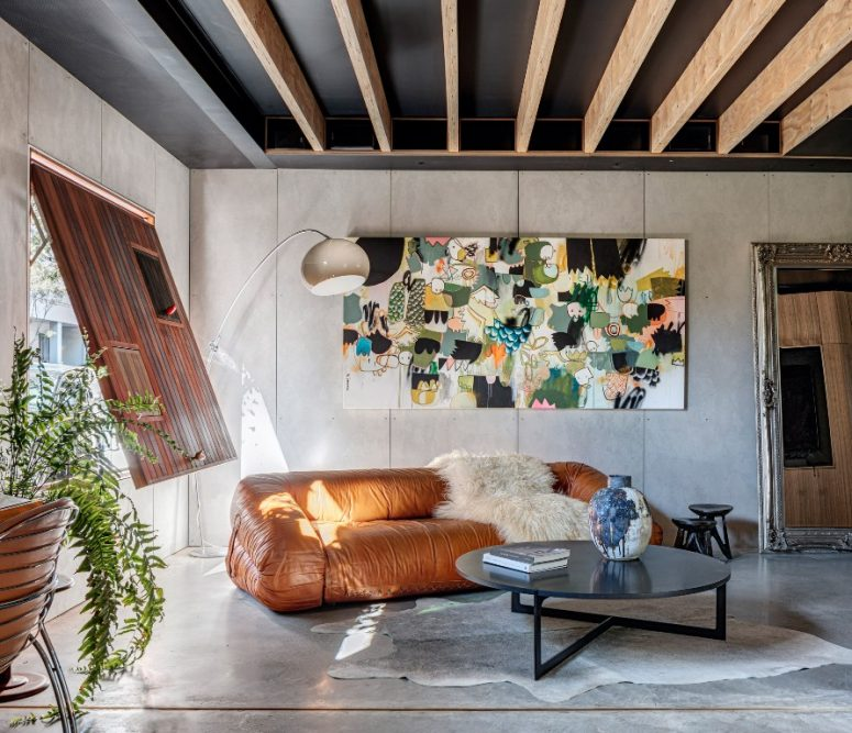 The living room shows off a unique artwork, a leather sofa and a wooden shutter with mini windows