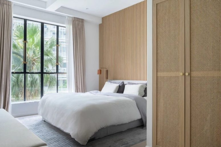 The master bedroom is done with a glazed wall, a wooden slab wall and delicate linens