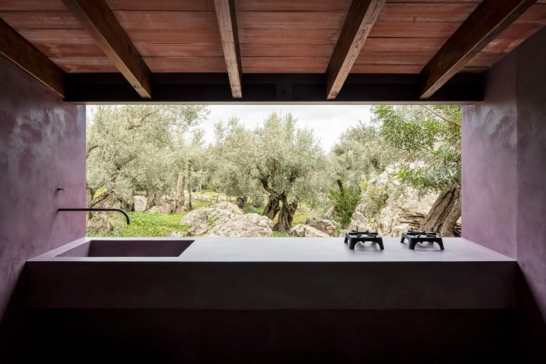 An outdoor-indoor kitchen and dining space shows off a carved sink and a cool view