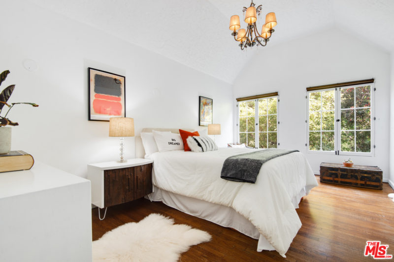 The bedroom is done with a vintage chandelier, eclectic furniture, lamps