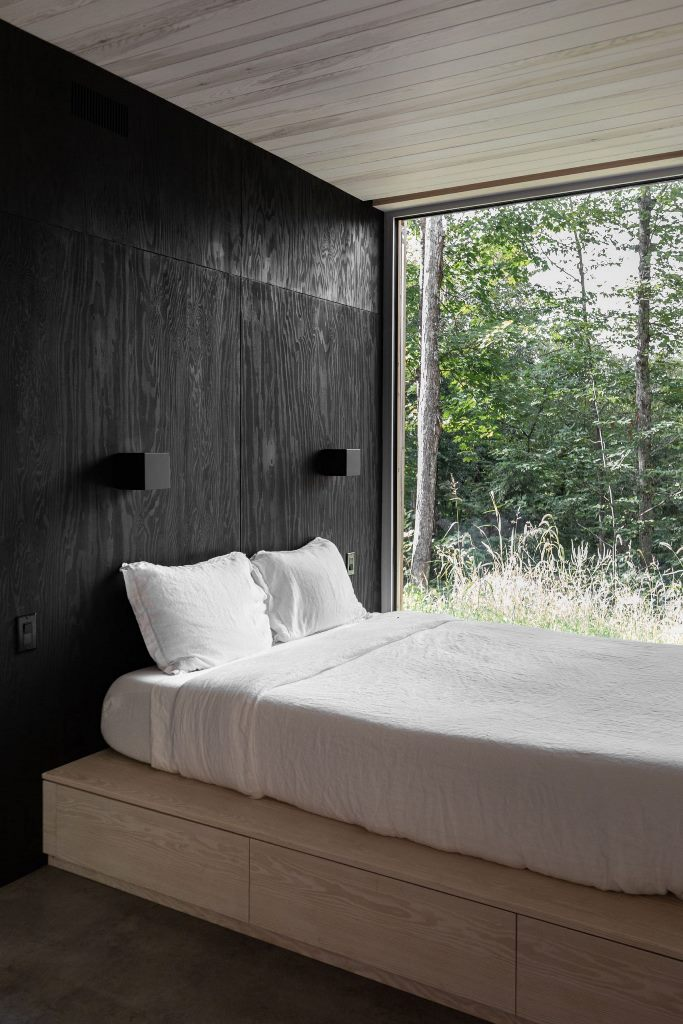 The bedroom is done with black walls, a platform bed with storage and a glazed wall