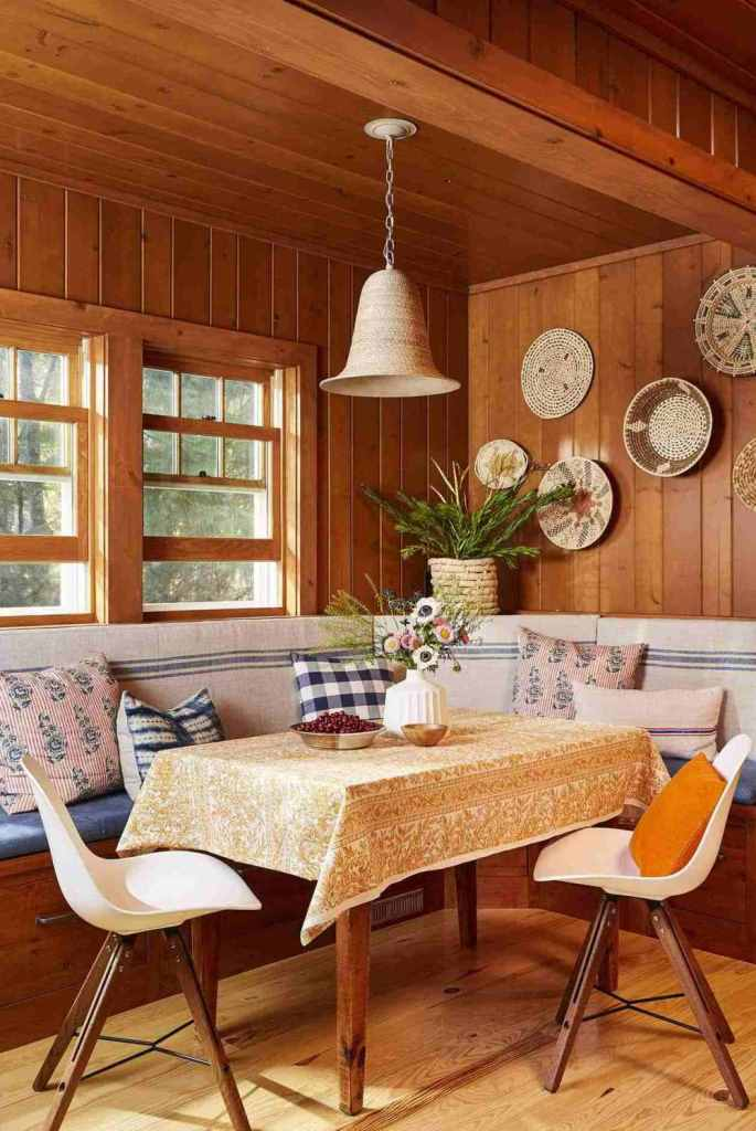The dining zone features a built-in seat with lots of pillows, chairs and a table
