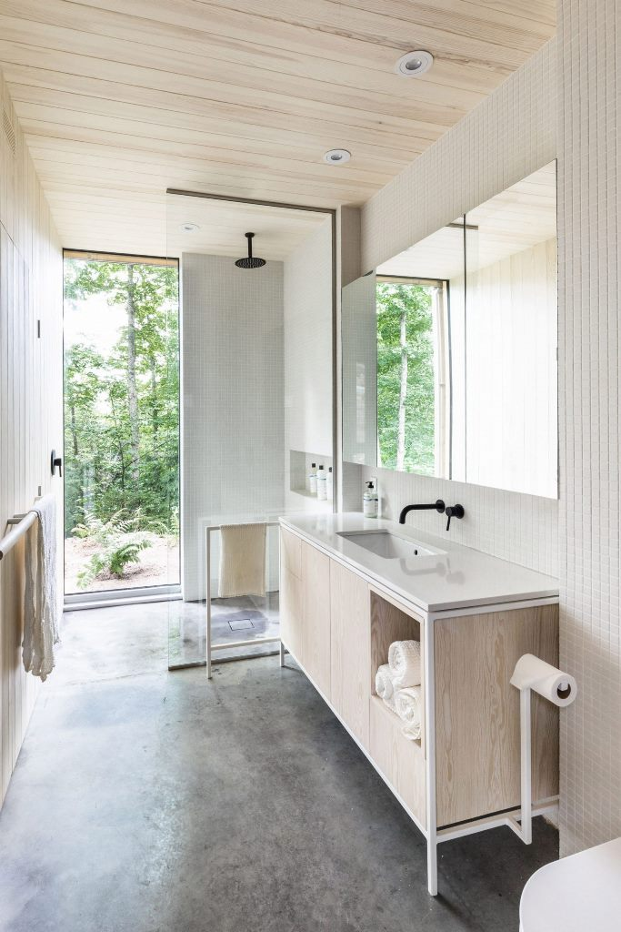 The bathroom is all-neutral, with white tiles and neutral plywood and a gorgeous forest view