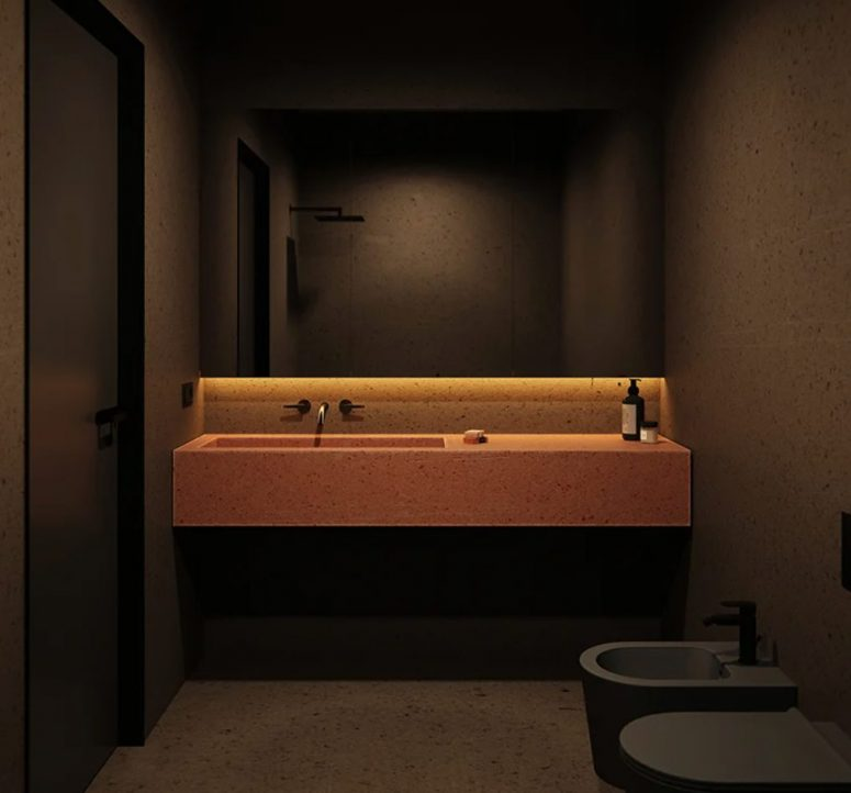 The bathroom is done in black, with a red pigment cement vanity and sink
