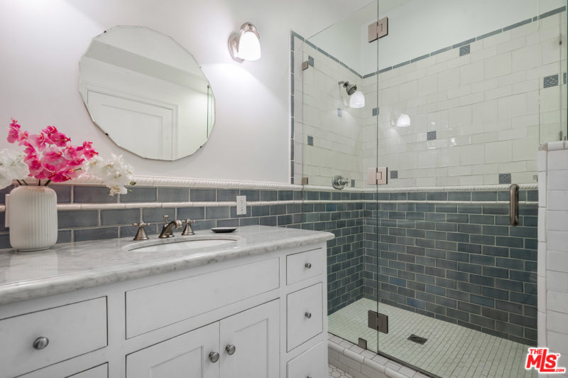 The bathroom is done with grey tiles, a vintage vanity with a white stone countertop