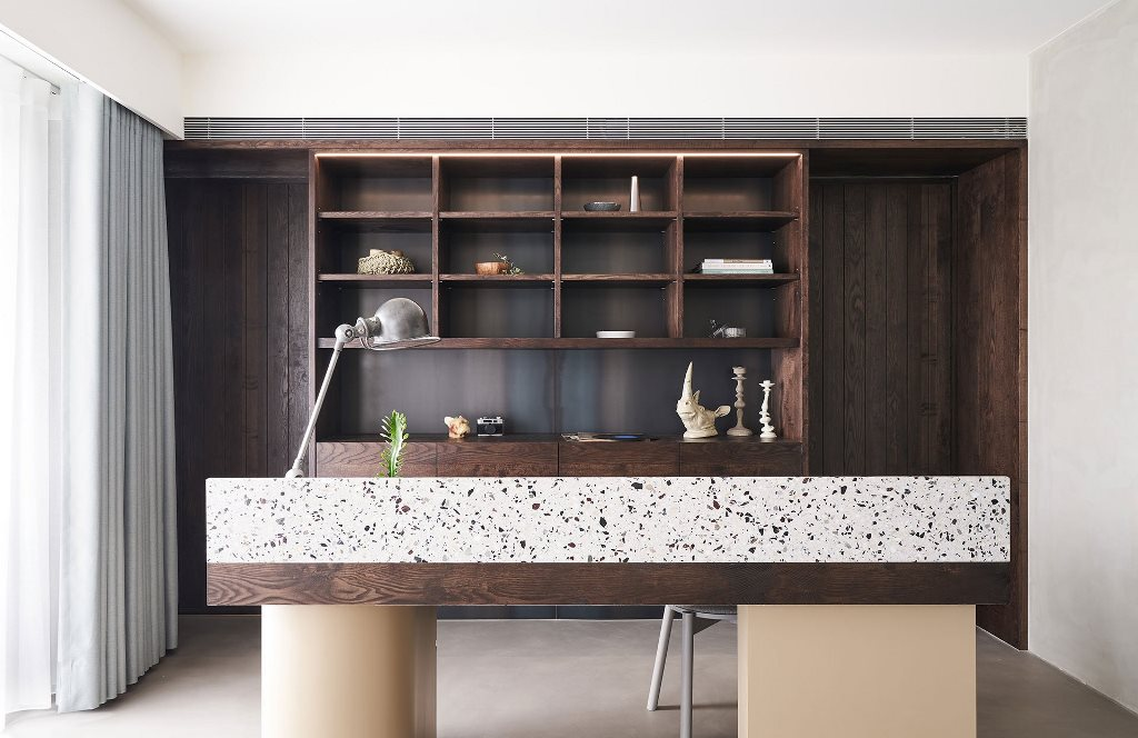 The home office is also here, with a large dark stained storage unit, a dark desk with terrazzo