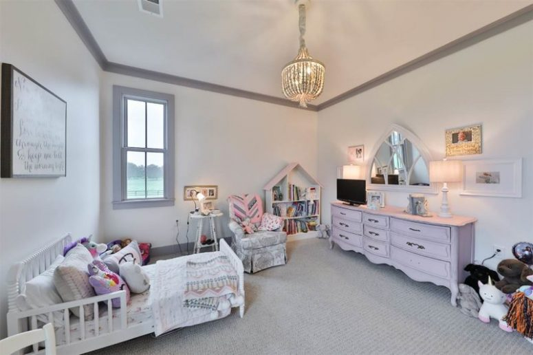 The kid's room is soft and pastel, with chic vintage furniture and a beautiful blush sideboard