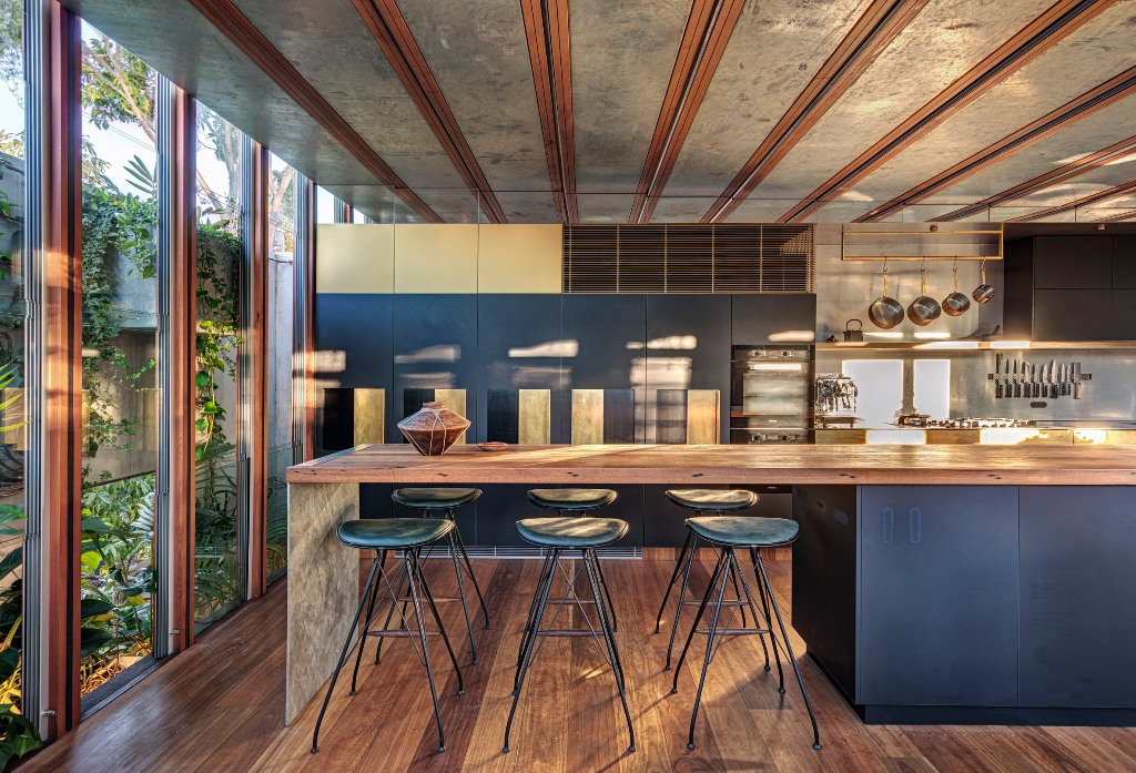 The kitchen is large and is done with dark metal and recycled timber, it feels very cozy with that much light