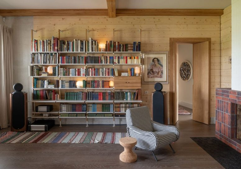 There's a large open shelf, a plaid chair and a fireplace for a cozy reading nook