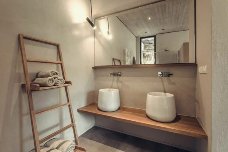 The bathroom features a floating vanity, two catchy sinks and some shelves