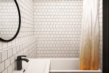 08 The bathroom is contemporary, with white tiles and black grout and more black accents for drama