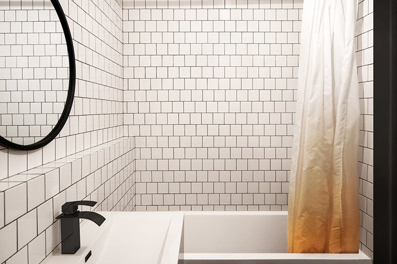 The bathroom is contemporary, with white tiles and black grout and more black accents for drama