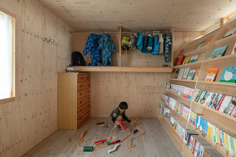 This is a creative kid's room with toys, a siddeboard, some holders and hangers under the ceiling
