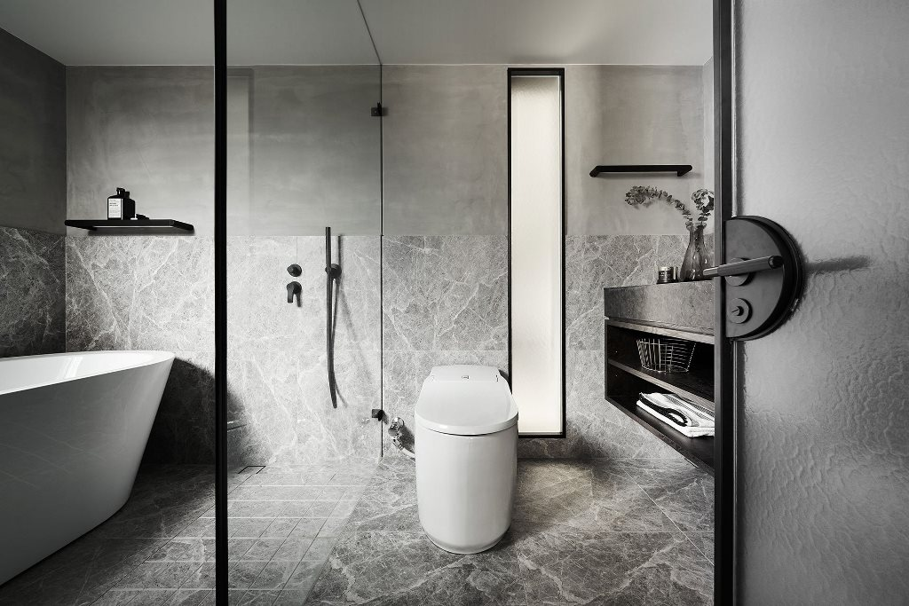The bathroom is done in grey, with white appliances and black touches