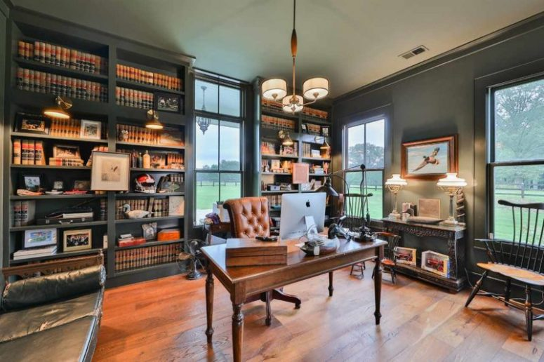 The home office is dark and moody, with built-in shelves, vintage furniture and pendant and table lamps in vintage style