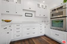 09 The kitchen is done in white, with chic traditional cabinets and black handles