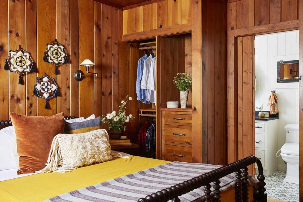 The master bedroom continues the decor of the rest of the house with stained wood and heavy furniture