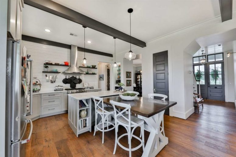 The kitchen is white, with a kitchen island and a trestle table that is attached to it for eating