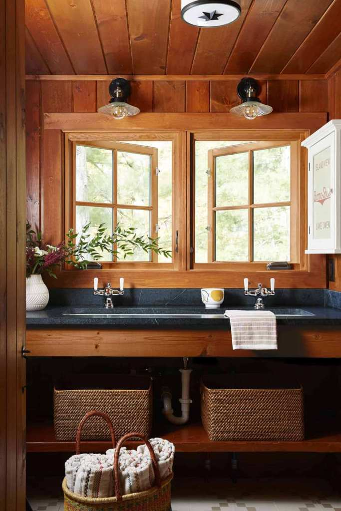 The master bathroom is done with stone countertops, baskets and flowers