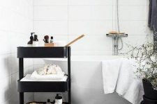 10 a black IKEA cart used for storage in a Scandinavian bathroom is a stylish piece to try