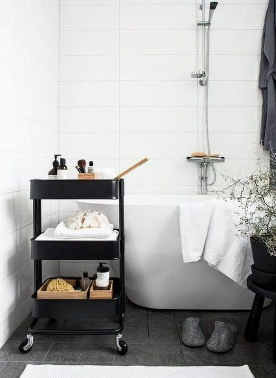 a black IKEA cart used for storage in a Scandinavian bathroom is a stylish piece to try