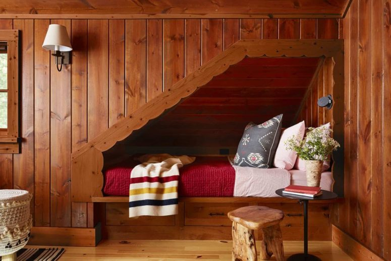 One more bedroom completely covered with wood, with stools and cozy lamps