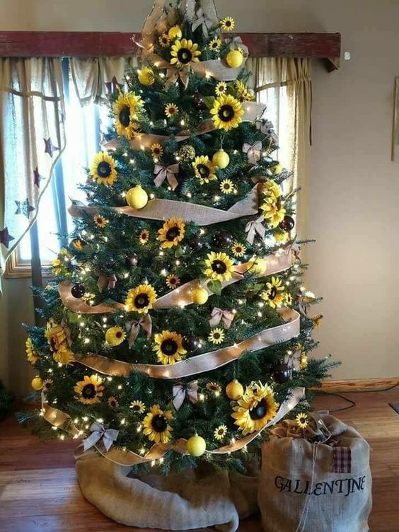 a fall tree decorated with faux sunflowers, lights, ribbon bows, burlap bows and bright yellow ornaments