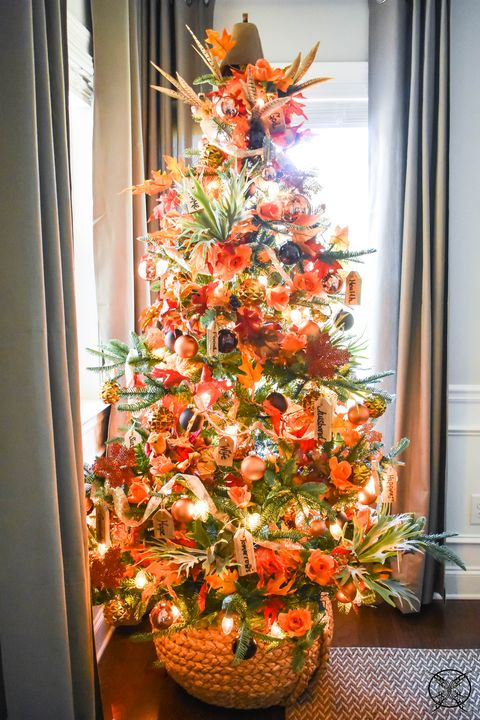 a gorgeous bright Thanksgiving tree with lights, ornage, gold and black ornaments, faux leaves, foliage and a pumpkin on top