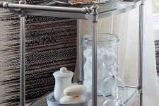 16 a refined stainless steel and glass rolling cart is a stylish storage piece with many items and some decor