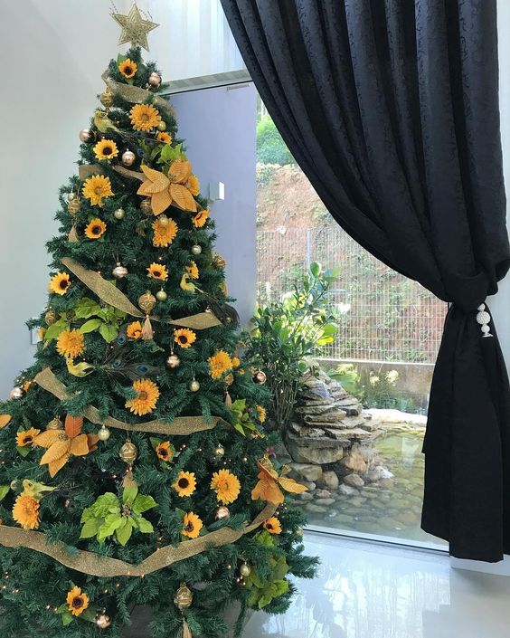 a stylish rustic Thanksgiving tree decorated with gold mesh ribbons, faux sunflowers, bright greenery and gold ornaments